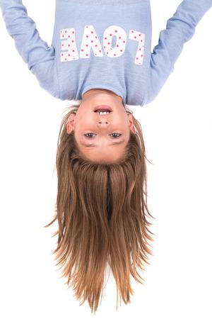 cabeza abajo: Chica joven boca abajo aislado en blanco Foto de archivo