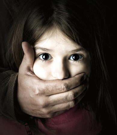 maltrato: Chica joven asustado con la mano de un hombre adulto tapándose la boca Foto de archivo