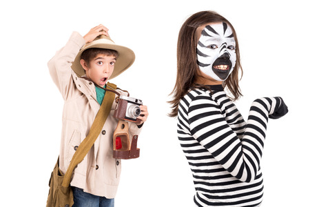 zebra face: Young girl with face painted like a zebra and boy explorer with camera