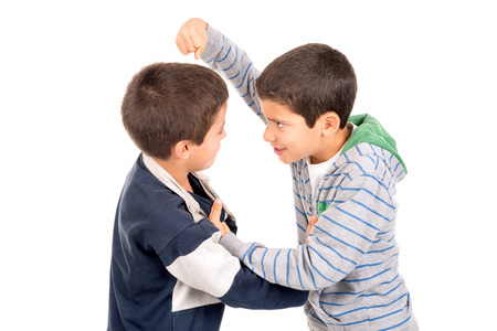 Young boys fighting isolated in white Foto de archivo