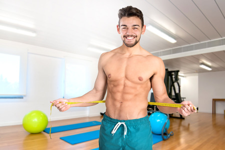 abdominals: Muscular and fit young man with great abdominals and measuring tape in the gym