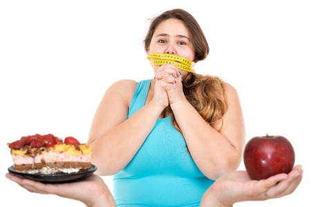 overweight people: Beautiful large girl gagged with measuring tape lokking at a cake and an apple isolated in white