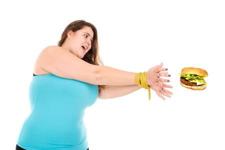 girl tied: Beautiful large girl tied with measuring tape reaching for a burger isolated in white