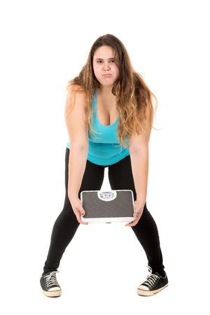 desesperado: Desesperado gran muchacha que sostiene una escala de peso aislado en blanco Foto de archivo
