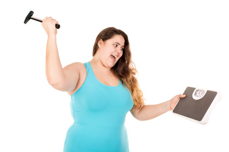 Desperate large girl punishing a weight scale with a hammer isolated in white