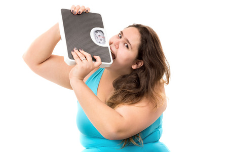 desperate: Desperate large girl biting a weight scale isolated in white