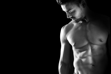 nude male body: Handsome young man, shirtless, with great body posing over a black background