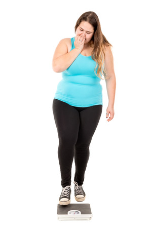 desperate: Desperate large girl with a weight scale isolated in white Stock Photo