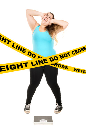 do not cross: Desperate large girl with a weight scale behind a do not cross weight line isolated in white Stock Photo