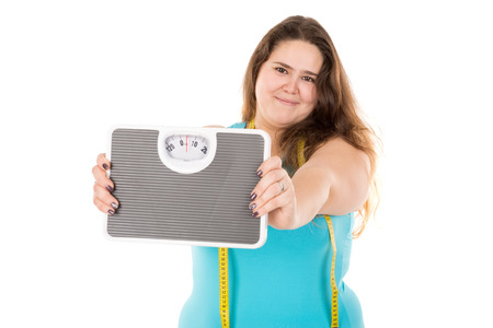 gluttonous: Beautiful large girl with measuring tape and weight scale isolated in white