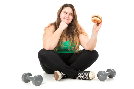 gluttonous: Large girl seated with dumbbells eating a hamburger isolated in white Stock Photo