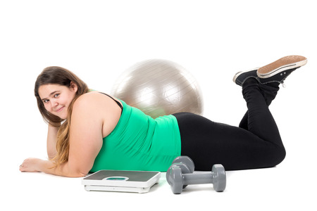 gluttonous: Beautiful large girl posing with an exercise ball dumbbells and weight scale