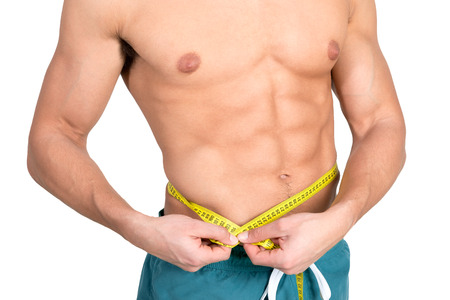 abdominals: Muscular and fit young man with great abdominals and measuring tape isolated in white