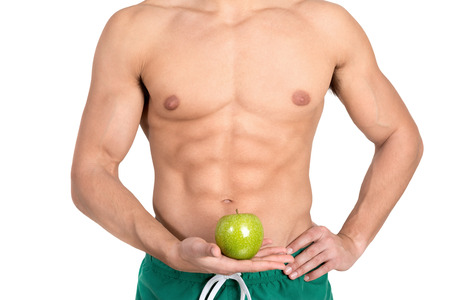 abdominal muscles: Mans abdominal muscles detail holding an apple isolated in white