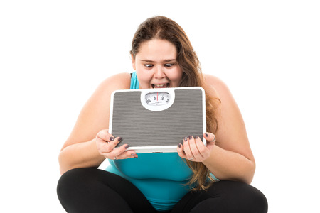 gluttonous: Desperate large girl biting a weight scale isolated in white