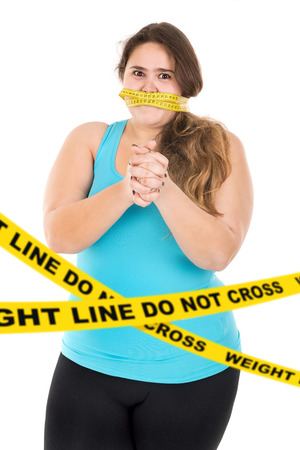 do not cross: Beautiful large girl gagged with measuring tape behind a do not cross weight line isolated in white