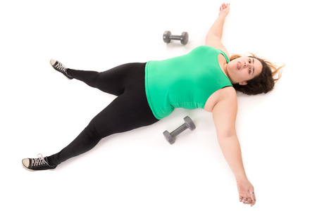 Tired large girl laying down after doing exercises with dumbbells isolated in white