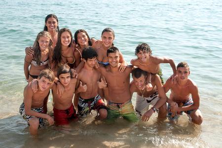 cara sonriente: Grupo de adolescentes felices en la playa Foto de archivo