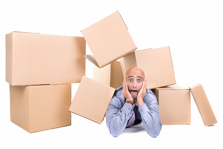 postal office: Stressed businessman under a pile of cardboard boxes Stock Photo