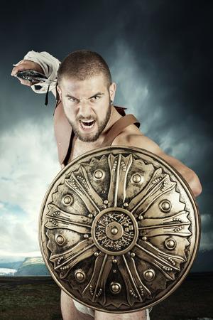 guerrero: Gladiador o guerrero posando con escudo y espada al aire libre listo para la batalla