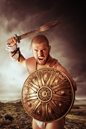 sword: Gladiator or warrior posing with shield and sword outdoors ready for battle