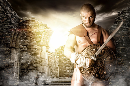 ancient warrior: Gladiator or warrior posing with shield and sword outdoors ready for battle
