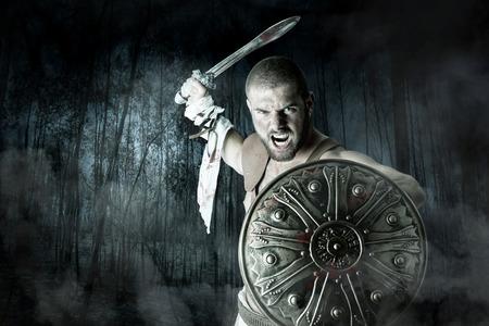 romano: Gladiador o guerrero posando con escudo y espada que lucha en un bosque oscuro