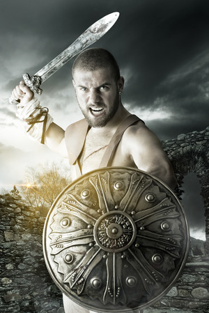 gladiator: Gladiator or warrior posing with shield and sword outdoors ready for battle