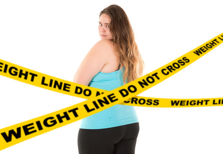 do not cross: Sad large girl posing on her back behind a do not cross weight line isolated in white