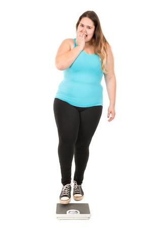 desesperado: Niña grande desesperada con una escala de peso aislado en blanco