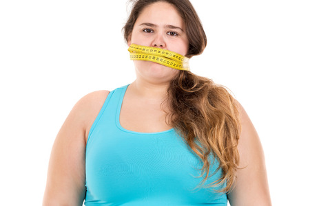 gagged: Beautiful large girl gagged with measuring tape isolated in white Stock Photo