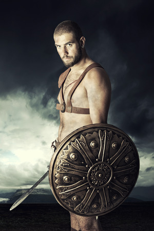 Gladiator or warrior posing with shield and sword outdoors ready for battle