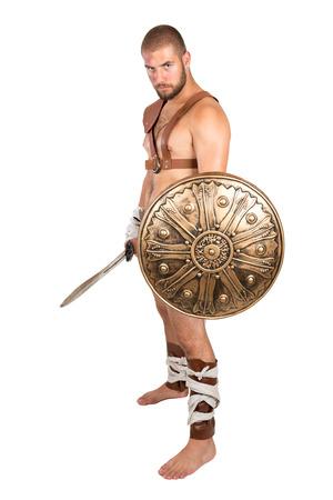 escudo: Gladiador posando con escudo y espada aislado en blanco Foto de archivo