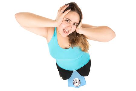 mujer gorda: gran chica desesperada gritando con una escala de peso aislado en blanco