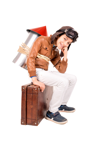 flight helmet: Young boy with home made rocket and suitcase ready for adventure
