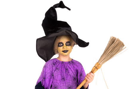 witch on broom: Girl with face-paint and Halloween witch costume isolated in white