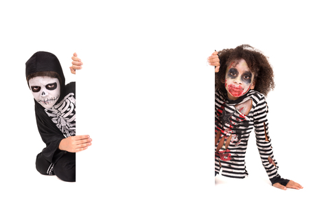 evil face: Kids with face-paint and Halloween costumes over a white board