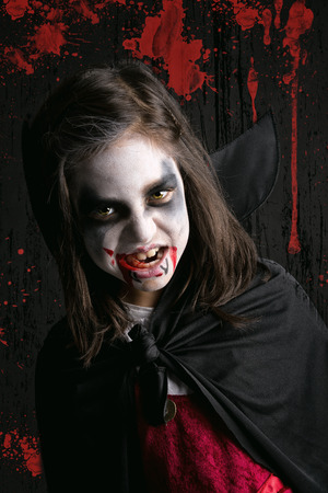 beautiful vampire: Girl with face-paint and Halloween vampire costume in a dark bloody background Stock Photo