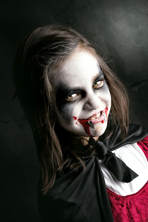 Girl with face-paint and Halloween vampire costume in a dark background