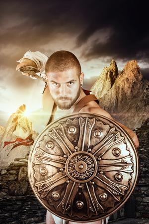 warrior: Gladiador o guerrero posando con escudo y espada al aire libre listo para la batalla