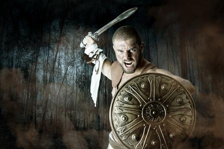 guerrero: Gladiador o guerrero posando con escudo y espada que lucha en un bosque oscuro
