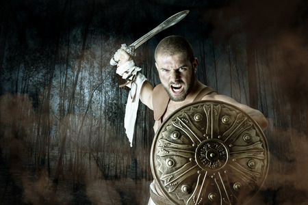 armour: Gladiator or warrior posing with shield and sword battling in a dark forest Stock Photo