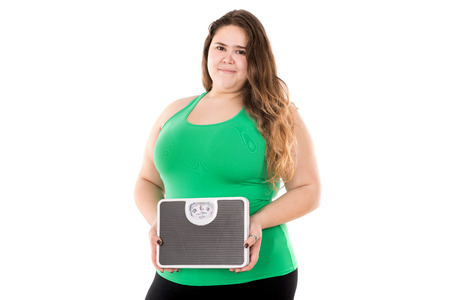 Beautiful large girl posing with a weight scale isolated in white