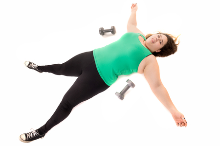 gluttonous: Tired large girl laying down after doing exercises with dumbbells isolated in white