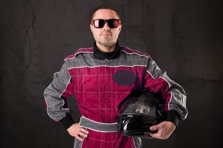 Rennfahrer posiert mit Helm auf einem Grunge-Hintergrund