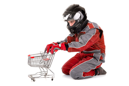 shopping cart isolated: Racing driver posing with shopping cart isolated in white