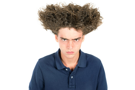 crazy hair: Angry teenage boy with crazy hair isolated in white