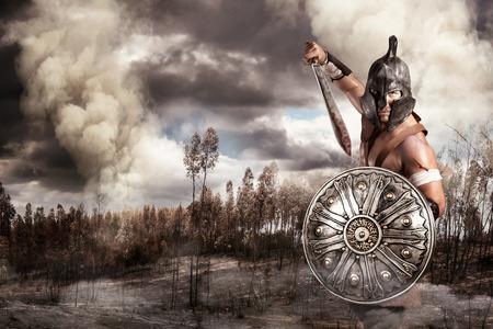 warrior: Gladiador en un campo de batalla en las montañas Foto de archivo