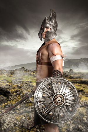 Ancient warrior posing outdoors with swords ready for battle Stock Photo