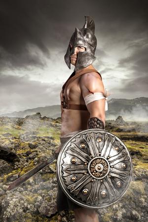Antico guerriero posa all'aperto con le spade pronte per la battaglia